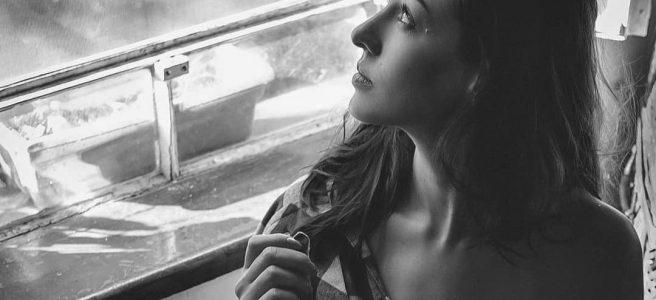 Moça olhando pela janela
